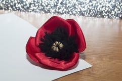 Dekorativ röd gjord vallmoblomma - satängtyg ligger på ett vitt ark av papper Fotografering för Bildbyråer