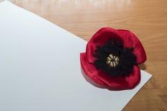 Dekorativ röd gjord vallmoblomma - satängtyg ligger på ett vitt ark av papper Royaltyfri Foto