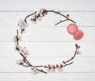 Dekorativ ram av blommor och makron på en vit träbaksida Arkivfoton