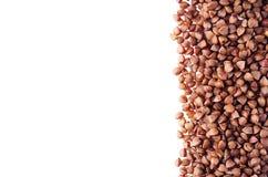Dekorativ ram av brun bovete på vit bakgrund Bästa sikt, closeup Fotografering för Bildbyråer