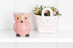 Dekorativ rosa Owl Moneybox och billig prydnadssak på den vita hyllan Royaltyfria Bilder