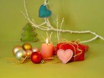 Dekorativ säsongsbetonad sammansättning av en brinnande stearinljus, filthjärtor, julgranbollar, juldekor, romantisk inre arkivfoto
