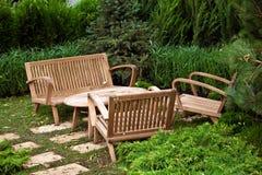 Dekorativ stolar och tabell i trädgården Arkivfoto