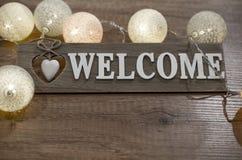 Dekorativ textvälkomnande med hjärta och ljus på trätabellen Royaltyfria Foton