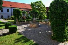 Dekorativ trädgårds- båge med spiralen för sten för sten den låga murral växande murgrönaHederapå konstruktion över, träbänkar oc Royaltyfria Foton