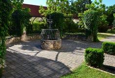 Dekorativ trädgårds- båge med spiralen för sten för sten den låga murral växande murgrönaHederapå konstruktion över, träbänkar oc Arkivfoto