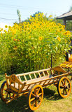 Dekorativ trävagn nära solrosor arkivbild