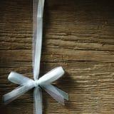 Dekorativ vit band och pilbåge över träbakgrund royaltyfri foto