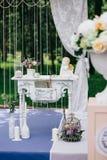 Dekorativ vit tappningtabell på bröllopceremonin, stearinljus-dekorerade böcker med blommor och keramiska vinklar och a Arkivfoto