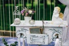 Dekorativ vit tappningtabell på bröllopceremonin, stearinljus-dekorerade böcker med blommor och keramiska vinklar och Arkivbild