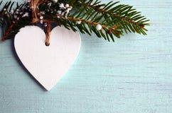 Dekorativ vit träjulhjärta och granträdfilial på blå träbakgrund med kopieringsutrymme Royaltyfri Foto