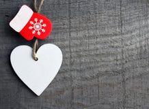 Dekorativ vit träjulhjärta och röd tumvante på grå lantlig träbakgrund med kopieringsutrymme Arkivbilder