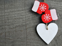 Dekorativ vit träjulhjärta och röda tumvanten på grå lantlig träbakgrund med kopieringsutrymme Royaltyfri Foto