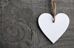 Dekorativ vit träjulhjärta på grå lantlig träbakgrund med kopieringsutrymme Arkivfoto