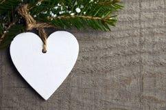 Dekorativ vit träjulhjärta på grå lantlig träbakgrund med kopieringsutrymme Royaltyfria Bilder