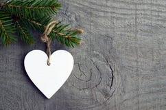 Dekorativ vit träjulhjärta på granträdfilial på grå lantlig träbakgrund med kopieringsutrymme Royaltyfria Bilder
