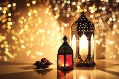 Dekorativa arabiska lyktor med brinnande stearinljus Blänka guld- bokehljus Platta med datumfrukt på tabellen arkivfoto