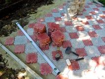 Dekorativa figurerade röd-och-vit stenläggningtegelplattor och hjälpmedel för att stenlägga det Royaltyfria Bilder