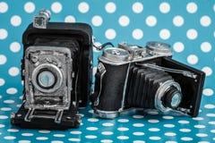 Dekorativa gamla antika kameror på blå bakgrund Fotografering för Bildbyråer