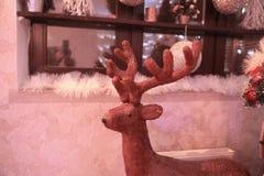 Dekorativa hjortar för jul på bakgrunden av en hemtrevlig vardagsrum royaltyfria bilder