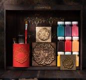 Dekorativa keramiska tegelplattor för stuckaturmurbruk, målarfärger och målarfärgborstar på en trähylla arkivfoton