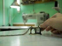 Dekorativa klockor i form av en symaskin på bakgrunden av denna symaskin arkivfoton