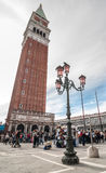 Dekorativa lyktstolpar i piazza San Marco mot campanile Arkivbild