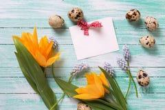 Dekorativa påskägg, blommor och tömmer etiketten på turkosträ Royaltyfri Bild