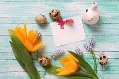 Dekorativa påskägg, blommor och tömmer etiketten på turkosträ Royaltyfria Bilder