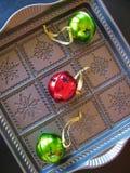 Dekorativa prydnader för för metallkakapanna och träd reflekterar glödet av julferierna Royaltyfri Foto