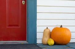 Dekorativa pumpa och kalebasser på den främre farstubron av ett hus arkivbild