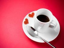 Dekorativa röda hjärtor nära koppen kaffe på den röda tabellen, begreppsvalentindag arkivbild