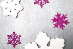 Dekorativa snöflingavit och rosa färger på grå bakgrund kortjul som greeting kopiera avstånd Top beskådar Arkivfoton