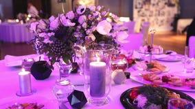 Dekorativa stearinljus på den äta middag tabellen, exponeringsglasen och julljusen på tabellen, vitt vaxcandleswithexponeringsgla lager videofilmer