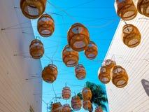 Dekorativa sväva lyktor hänger ovanför en bakgata i Malibu Royaltyfri Bild