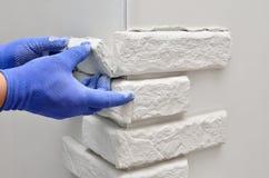 Dekorativa tegelplattor för belägen mitt emot vägg, arbetare i blå handske Royaltyfri Bild
