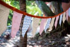 Dekorativa triangulära och fyrkantiga partiflaggor och lampor på träd som tonas och med olika modeller, med oskarp gräsplan arkivfoto