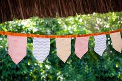 Dekorativa triangulära och fyrkantiga partiflaggor och lampor på träd som tonas och med olika modeller, med oskarp gräsplan fotografering för bildbyråer