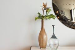 Dekorativa vaser på tabellen med den runda spegeln i bakgrundssnut Arkivbild