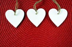 Dekorativa vita trähjärtor på röd sugrörservettbakgrund med kopieringsutrymme Royaltyfri Bild