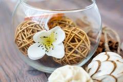Dekorative Bälle und getrocknete Orange in der Glaskugel mit Zimt auf einem Holztisch mit einer Vielzahl von schönen Einzelteilen Lizenzfreies Stockfoto