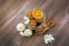 Dekorative Bälle und getrocknete Orange in der Glaskugel mit Zimt auf einem Holztisch mit einer Vielzahl von schönen Einzelteilen Lizenzfreie Stockfotografie