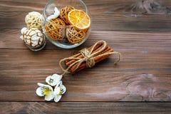 Dekorative Bälle und getrocknete Orange in der Glaskugel mit Zimt auf einem Holztisch mit einer Vielzahl von schönen Einzelteilen Stockfotografie