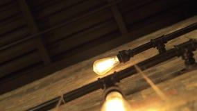 Dekorative Birne der glühenden Lampe, die an der Backsteinmauer hängt Helles Glühen hell von der Weinleselampe auf Wand Retro- Wo stock video footage