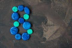 Dekorative blaue Steine formten Nr. acht auf einem dunklen Hintergrund Lizenzfreie Stockfotografie