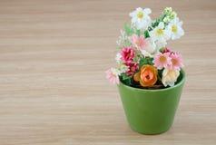 Dekorative Blume auf hölzernem Schreibtisch Stockfoto