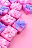 Dekorative Feriengeschenkkästen mit rosa Farbe auf rosa Hintergrund Stockbilder