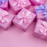 Dekorative Feriengeschenkkästen mit rosa Farbe auf rosa Hintergrund Lizenzfreie Stockbilder
