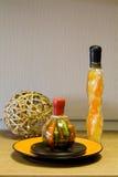 Dekorative Flaschen, Strohkugel und die keramische Platte Lizenzfreie Stockbilder