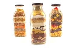 Dekorative Glasflaschen mit den verschiedenen Samen lokalisiert auf Weiß Stockbild